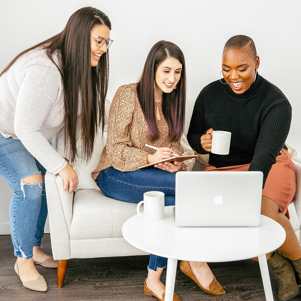 three diverse women drinking coffee and surrounding a laptop on and end table working on new website content