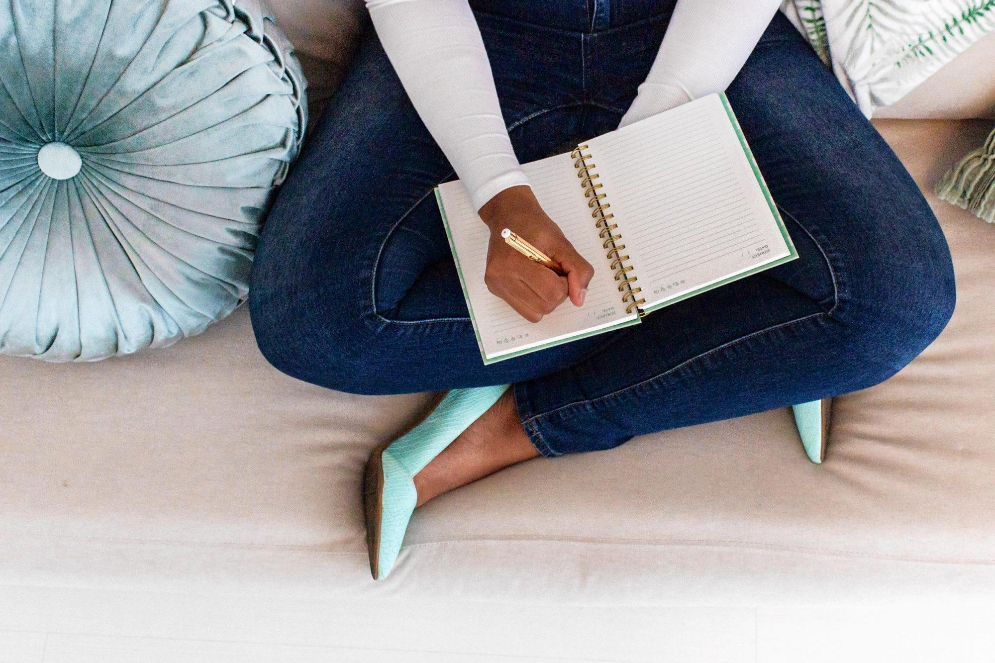black woman sitting cross legged on the floor with mint high heels and jeans next to a mint pillow doing some content writing