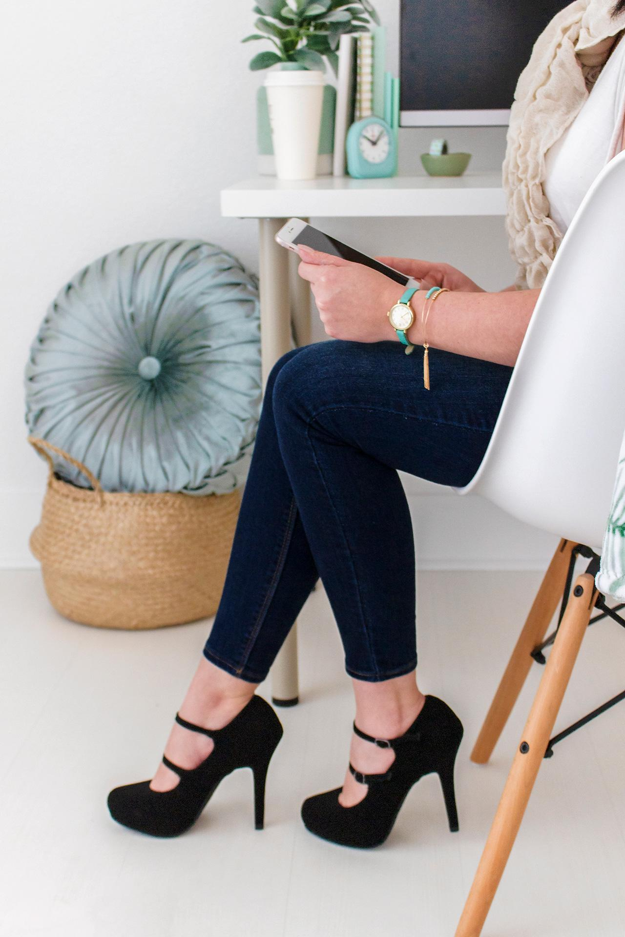 woman sitting on a white chair at an office desk searching on her iPad
