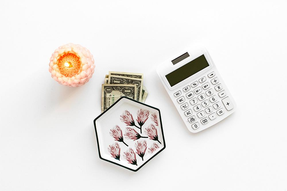 cash beneath a hexagon shaped small plate next to a candle and a calculator